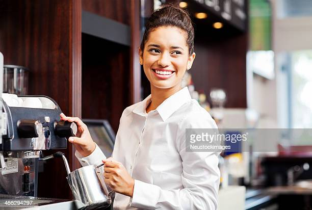 Serveuse regardant loin tout en fumant lait d'une cafetière électrique