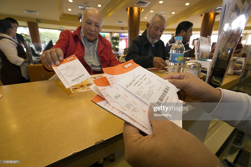 A waitress looks through customer checks at a Vips restaurant in the El Toreo neighborhood of Mexico City, Mexico, on Monday, June 17, 2013. Wal-Mart de Mexico SAB de CV, known as Walmex, is considering offers to sell its restaurant division, which includes the Vips, El Porton, Ragazzi and La Finca brands. Photographer: Susana Gonzalez/Bloomberg via Getty Images