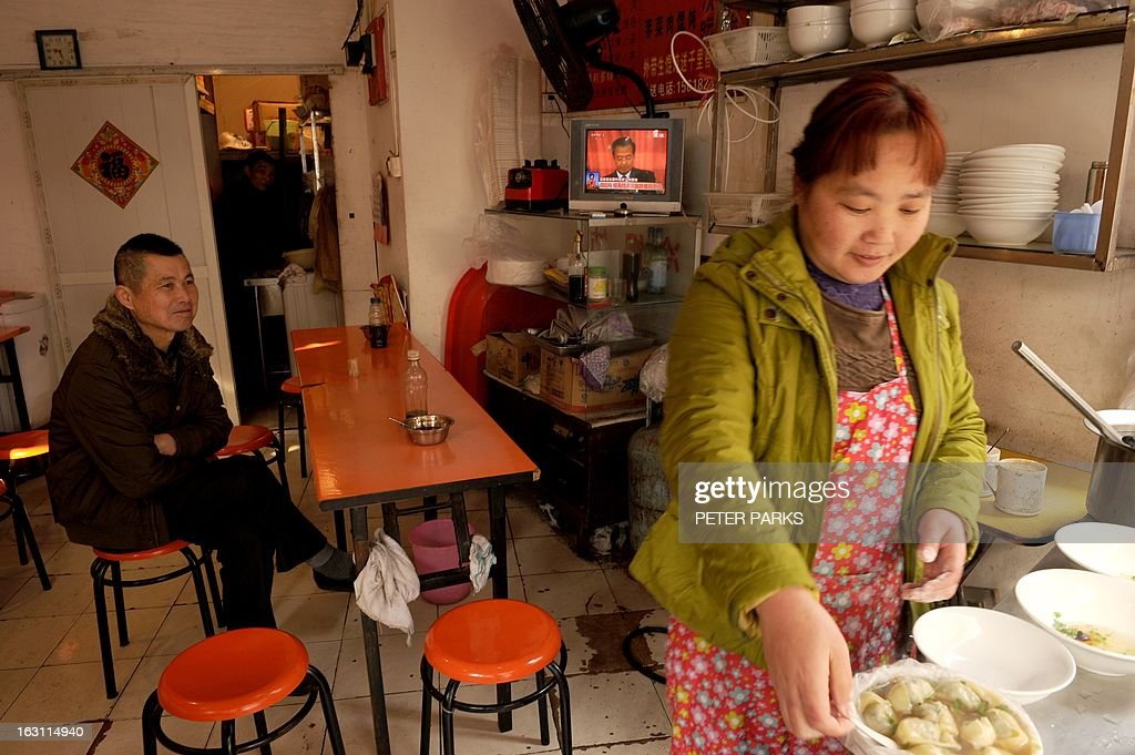 A waitress (R) makes dumplings for a customer (L) as a television set shows Chinese Premier Wen Jiabao (C) speaking at the opening session of the National People's Congress (NPC), at a small restaurant in Shanghai on March 5, 2013. Premier Wen targeted 2013 growth of 7.5 percent and vowed an unwavering fight against corruption as the world's second-largest economy opened its annual parliamentary session. AFP PHOTO/Peter PARKS