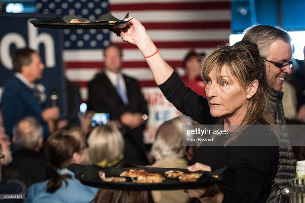 A waitress navigates the crowd at Finn's Brick Oven Pizza while Republican presidential candidate John Kasich talks during a campaign stop on February 10, 2016 in Mt. Pleasant, South Carolina. The South Carolina Republican primary will be held February 20, 2016.