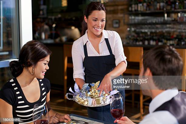 Waitress offering diners dessert tray