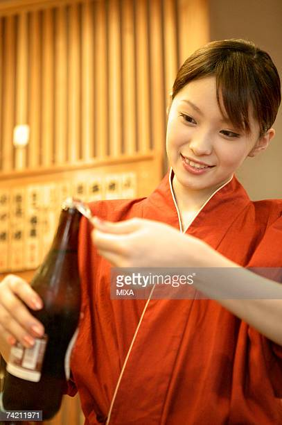 Waitress opening beer bottle