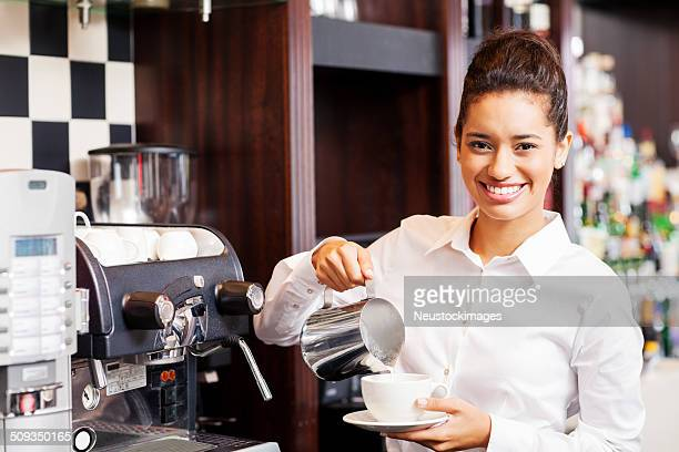 Waitress Pouring Milk In Coffee Cup At Restaurant