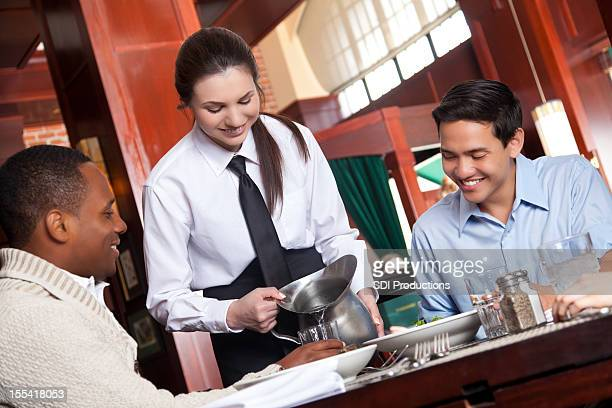 Waitress pouring water to customers in nice restaurant