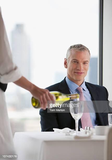 Empregada de Mesa Verter Vinho Branco para Empresário no restaurante