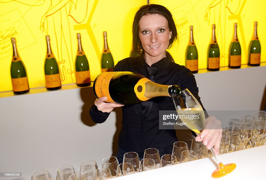 A waitress pours champagne into glasses at the Burda Style Group Cocktail on January 17, 2013 in Berlin, Germany.