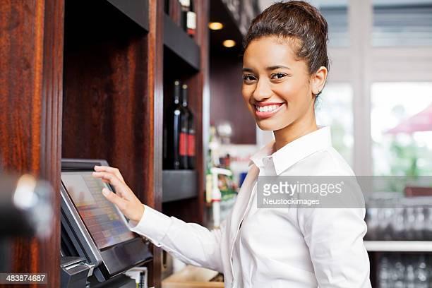 Serveuse préparer la facture à caisse enregistreuse au Restaurant