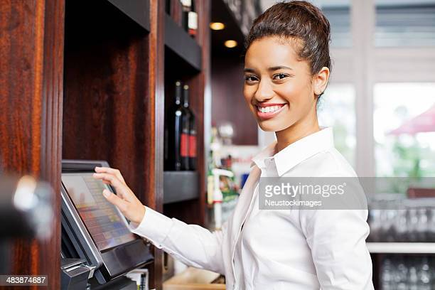 Kellnerin Vorbereitung Rechnung an Cash Register im Restaurant