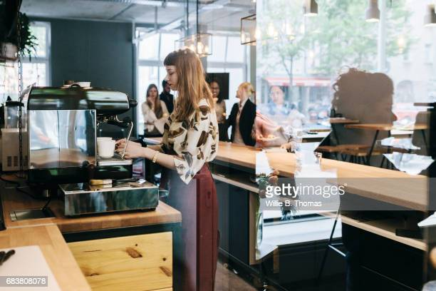 Waitress Preparing Coffee At Business Cafe Counter