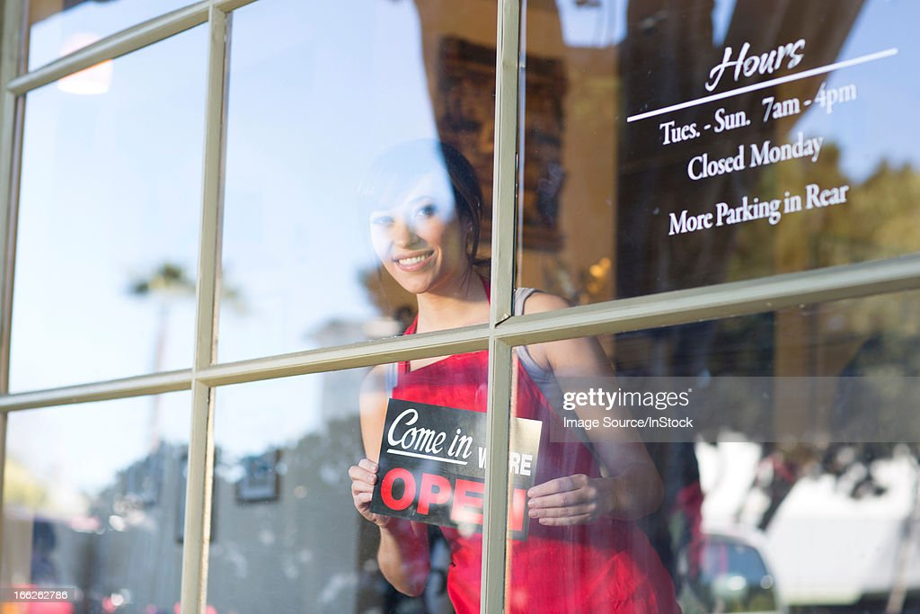 Waitress putting open sign in window : Stock Photo