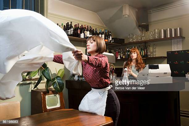 Waitress putting table cloth on table.
