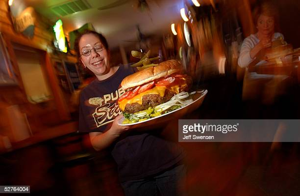 Waitress Rachel Pittman hustles a burger to waiting customers at Denny's Beer Barrell in Clearfield Pennysylvania The establishment features a 15...