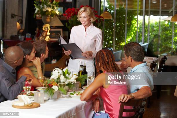 Waitress reading specials to people in restaurant