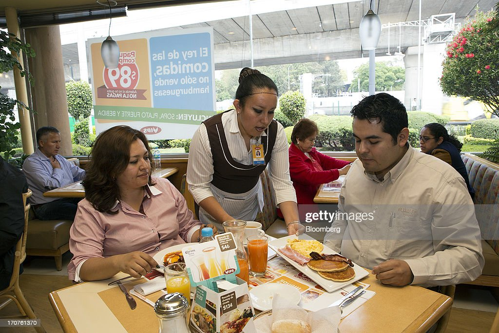 A waitress serves breakfast to customers at a Vips restaurant in the El Toreo neighborhood of Mexico City, Mexico, on Monday, June 17, 2013. Wal-Mart de Mexico SAB de CV, known as Walmex, is considering offers to sell its restaurant division, which includes the Vips, El Porton, Ragazzi and La Finca brands. Photographer: Susana Gonzalez/Bloomberg via Getty Images
