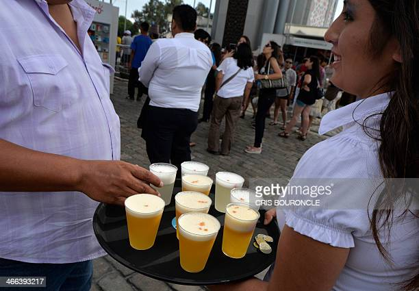 A waitress serves Pisco Sour in a street festival in Lima on February 1 during celebrations for the national Day of Pisco Sour an alcohol cocktail...