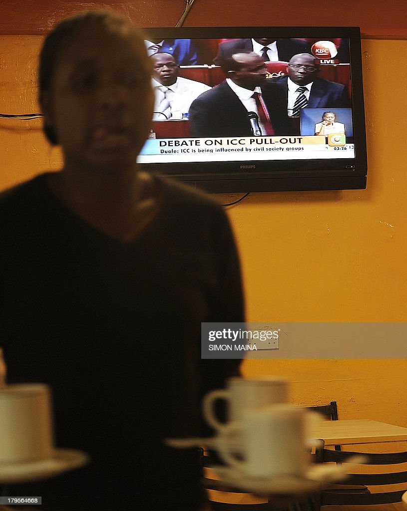 A waitress serves tea at a restaurant in Nairobi on September 5,2013 as local televsion broadcasts live proceedings on parliament disccussion on pulling out of the International Criminal Court (ICC). Kenyan lawmakers on September 5 began debating whether the country should pull out of the ICC, in an angry snub to The Hague-based tribunal ahead of next week's trial of Vice President William Ruto. Ruto on September 10 will be in The Hague to face three counts of crimes against humanity for allegedly organizing 2007-2008 post-election unrest that killed at least 1,100 people and displaced more than 600,000. His trial comes about two months ahead of that of President Uhuru Kenyatta, who faces five charges of crimes against humanity, including murder, rape, persecution and deportation.