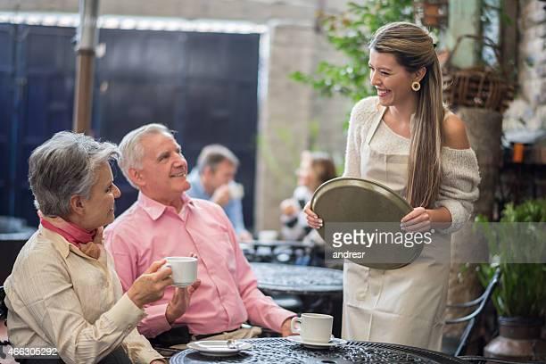 Kellnerin serviert ein altes Paar