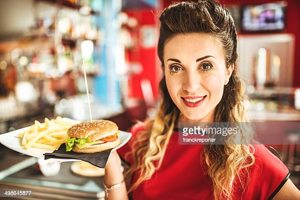 waitress serving an hamburger with french fries
