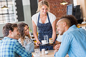 Happy smiling waitress serving food to a young happy group of friends in a cafeteria. Waitress serving on tray coffee to customers. Happy satisfied woman serving capuccino to group of multiethnic stud
