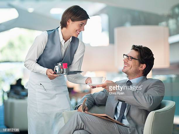 Waitress serving businessman cup of coffee in hotel lounge