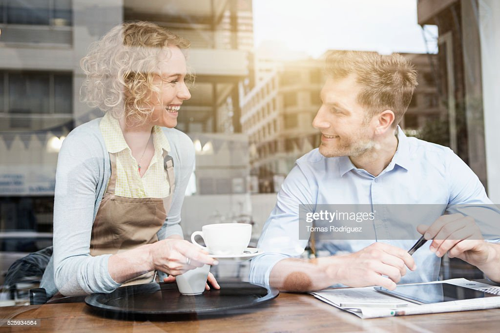 Waitress serving coffee cup to man at cafe : Stock Photo
