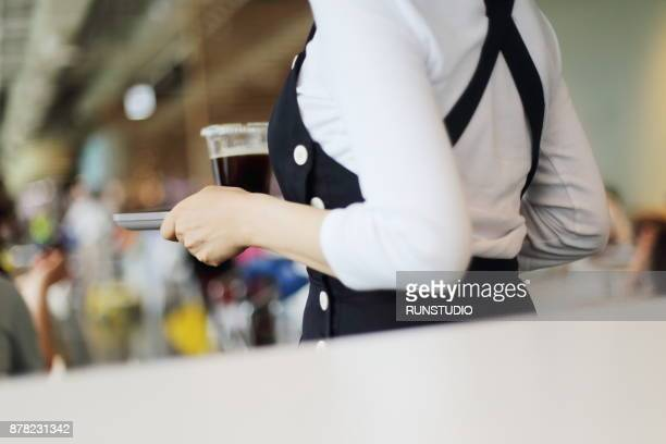 Waitress serving coffee in cafe