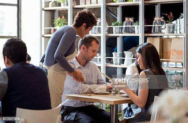 Waitress serving couple at a restaurant