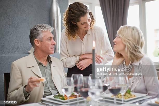 Waitress serving couple in restaurant