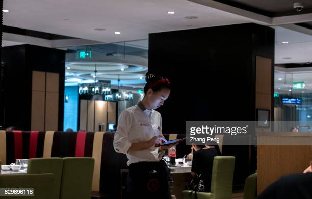 A waitress serving customers at a Haidilao restaurant Haidilao is China's most famous hotpot catering brand known its delicate service and used as...