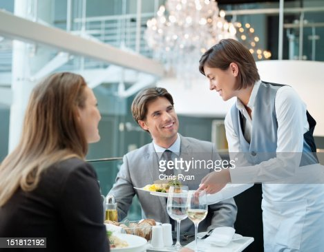 Waitress serving food to couple in restaurant