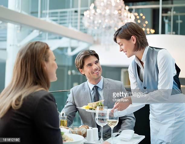 ウェイトレスのお料理をお出しするレストランのカップル