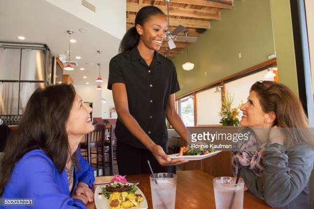 Waitress serving food to customers in restaurant