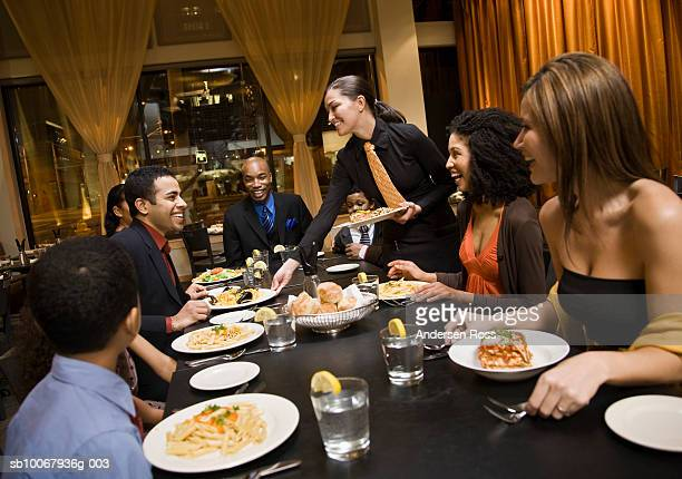 Waitress serving food to group of people in restaurant