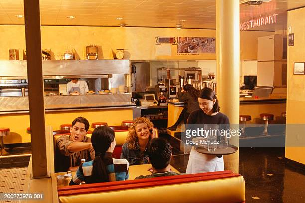 Waitress serving group of friends in cafe, elevated view