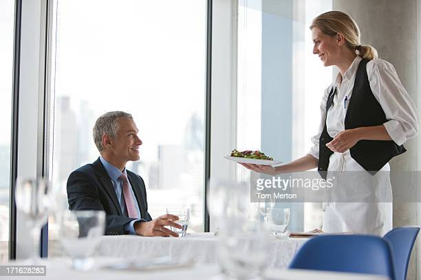 Waitress serving meal to businessman in restaurant