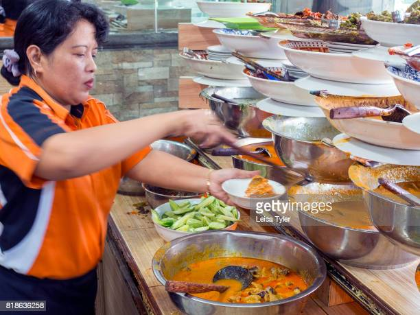 GARUDA MEDAN SUMATRA INDONESIA A waitress serving out a variety of dishes at Restoran Garuda a Nasi Padang restaurant in Medan Indonesia Steamed rice...
