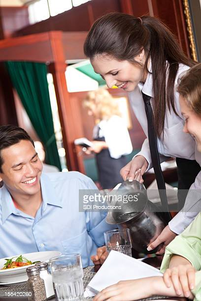 Waitress serving restaurant guests with drinking water