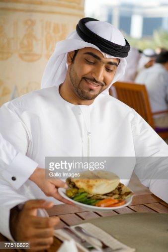 Waitress Serving Smiling Arab Man Lunch in Café. Dubai, United Arab Emirates