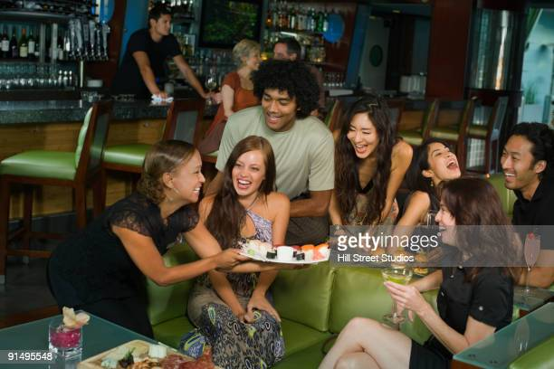 Waitress serving sushi to friends in nightclub