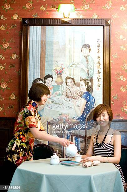 Waitress serving tea to Liu Yi at '1931' restaurant against wall painting on September 15 2009 in Shanghai China