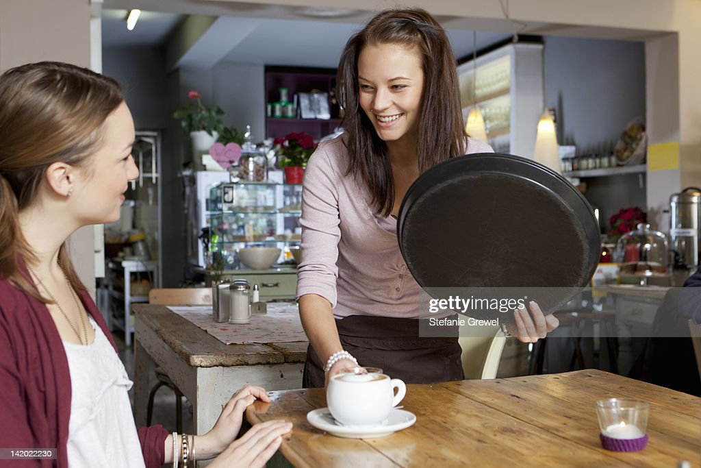 Waitress serving woman in cafe