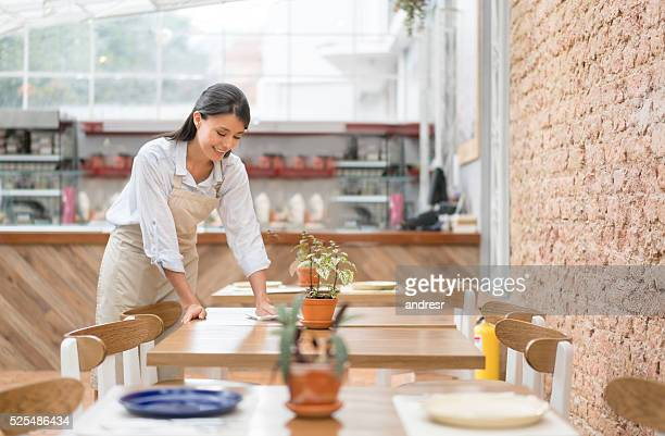 Waitress setting a table at a restaurant