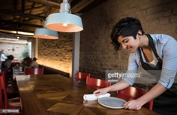 Waitress setting a table at a restaurant