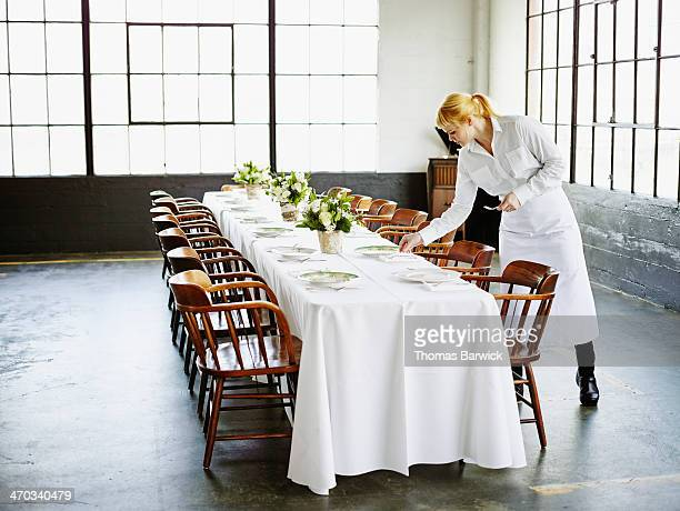 Waitress setting banquet table for dinner party