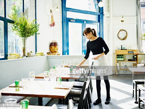 Waitress setting table in restaurant