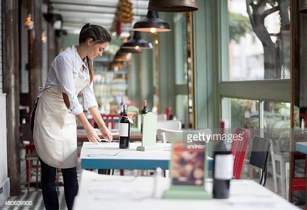 Waitress setting tables at a restaurant