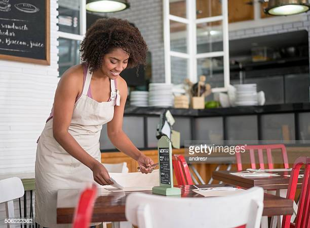 Waitress setting the table at a restaurant