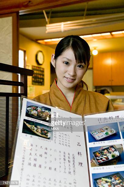 Waitress showing menu at Japanese restaurant