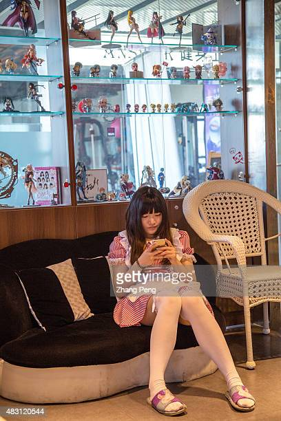 A waitress sits under the shop window displaying Japanese comic model kits A cosplay theme restaurant in Sanlitun Soho is a popular social place for...