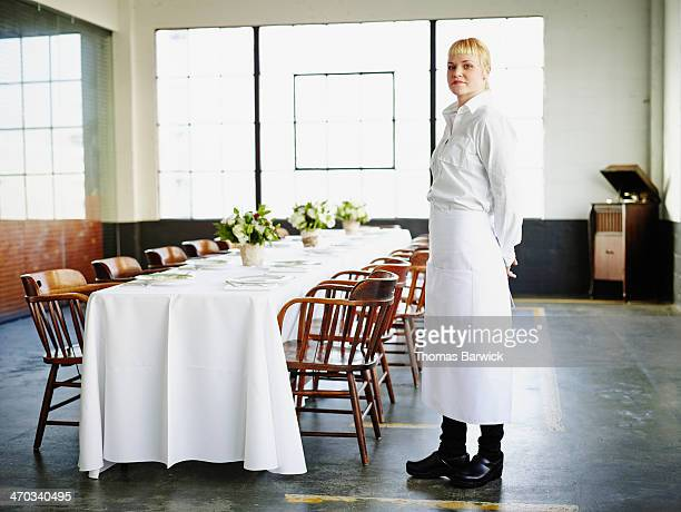 Waitress standing in front of set banquet table